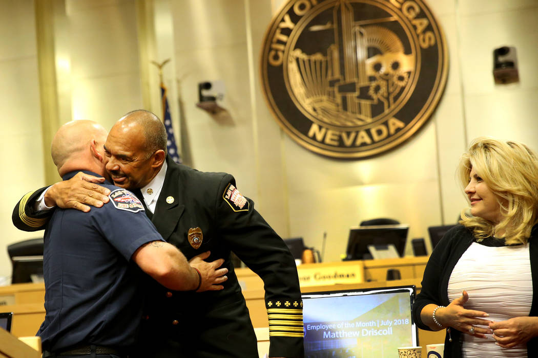 Las Vegas Fire and Rescue Chief William McDonald, right, embraces paramedic Matthew Driscoll, who was recognized as the employee of the month, during a city council meeting at Las Vegas City Hall ...