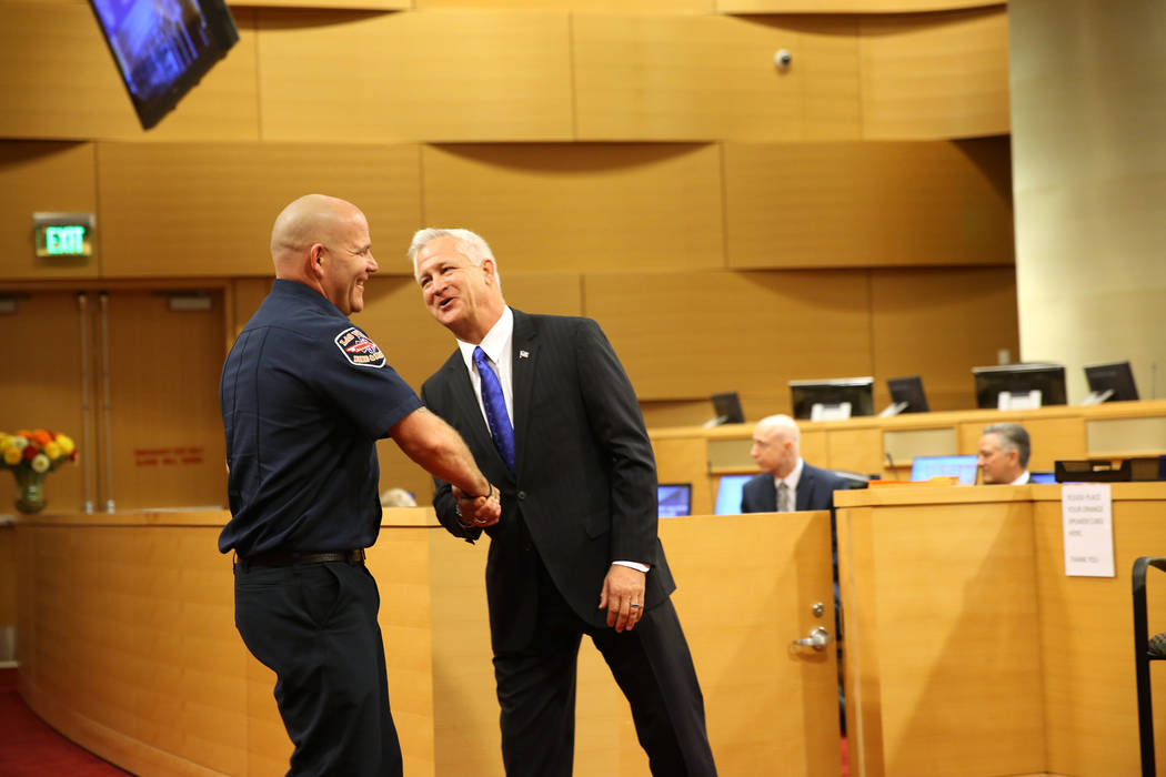 Las Vegas Councilman Steven Seroka, right, shakes hands with paramedic Matthew Driscoll, who was recognized as the employee of the month, during a city council meeting at Las Vegas City Hall in La ...
