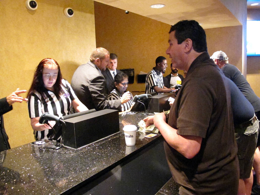 James Prendergast of Washington Township in northwestern New Jersey places bets on teams to win the Super Bowl at Harrah's casino in Atlantic City N.J. moments after it started accepting sports be ...