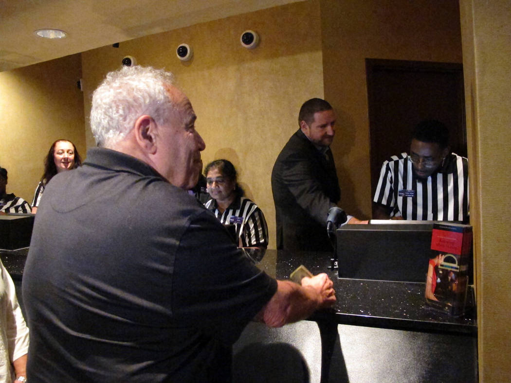 Alan Kallman places the first sports bet at Harrah's casino in Atlantic City N.J. on Wednesday Aug. 1, 2018. He put $25 on the New York Yankees to win the World Series. (AP Photo/Wayne Parry)