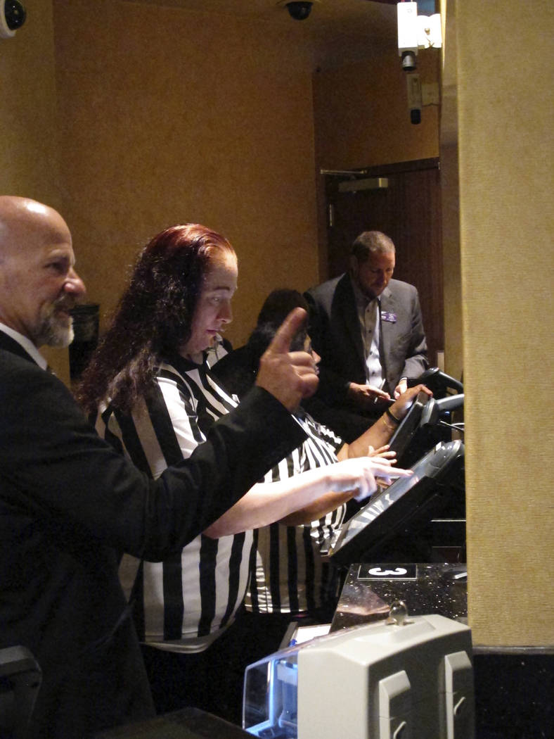 Employees of the new sports book at Harrah's casino in Atlantic City N.J. process wagers for customers moments after the casino started accepting sports bets on Wednesday Aug. 1, 2018. (AP Photo/W ...