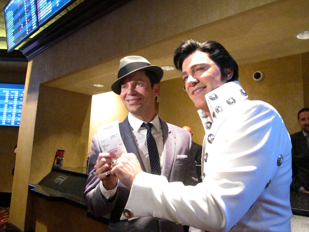 Frank Sinatra impersonator Brian Duprey, left, and Elvis Presley impersonator Kevin Mills, right, show off a ticket for a bet they placed on the New York Yankees moments after Harrah's casino in A ...