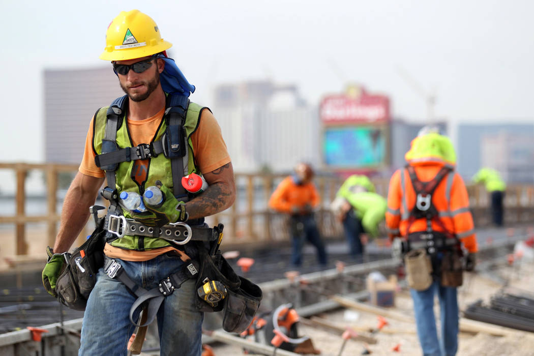 A worker grabs bottles of water while working on Nevada Department of Transportation Project Neon on Interstate 15 between the Spaghetti Bowl and Sahara Avenue Thursday, Aug. 2, 2018. K.M. Cannon ...