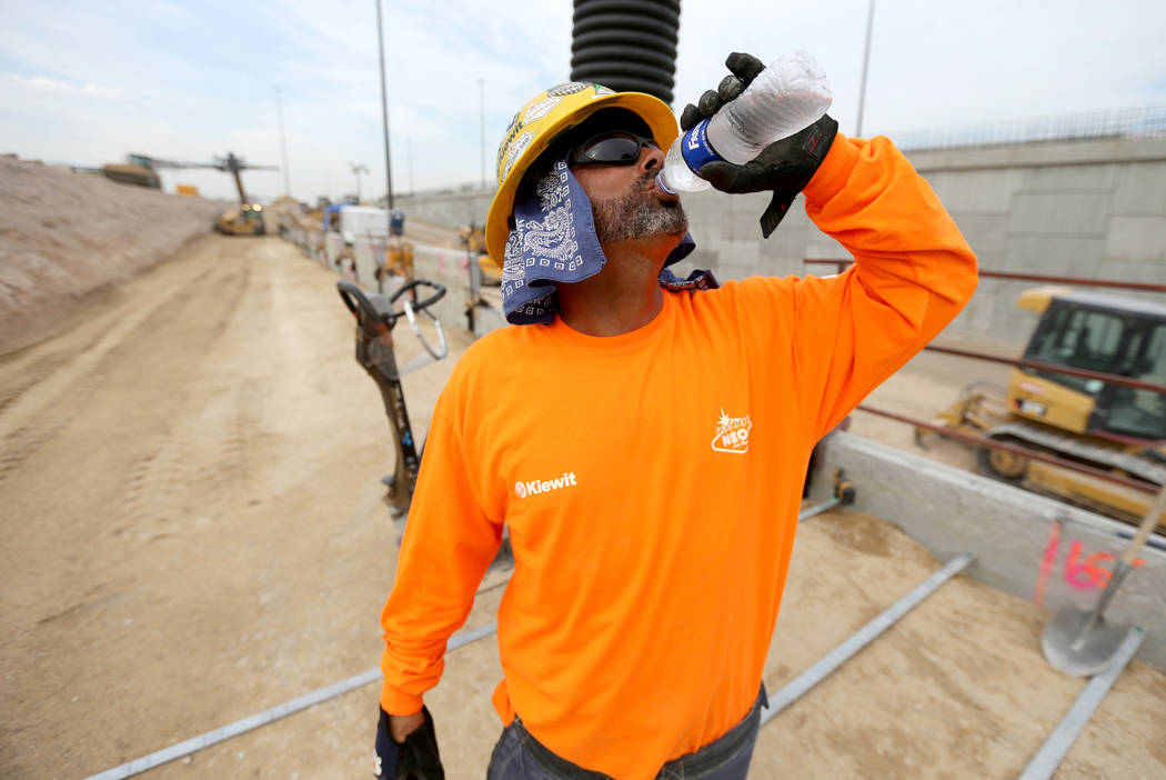 """Thomas Farino drinks water while working on a retaining wall for the """"Neon Gateway"""" high-occupancy vehicle exit ramps as part of Nevada Department of Transportation Project Neon on Inter ..."""