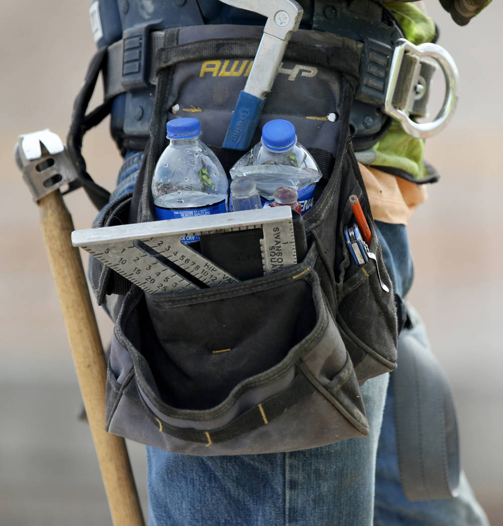 A worker carries bottles of water while working on Nevada Department of Transportation Project Neon on Interstate 15 between the Spaghetti Bowl and Sahara Avenue Thursday, Aug. 2, 2018. K.M. Canno ...