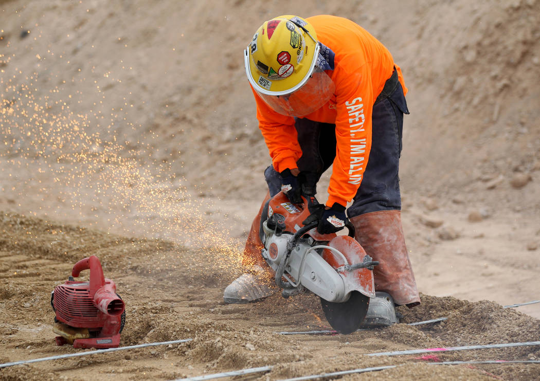 Thomas Farino cuts metal straps that will help hold a retaining wall in place on Nevada Department of Transportation Project Neon on Interstate 15 between the Spaghetti Bowl and Sahara Avenue Thur ...