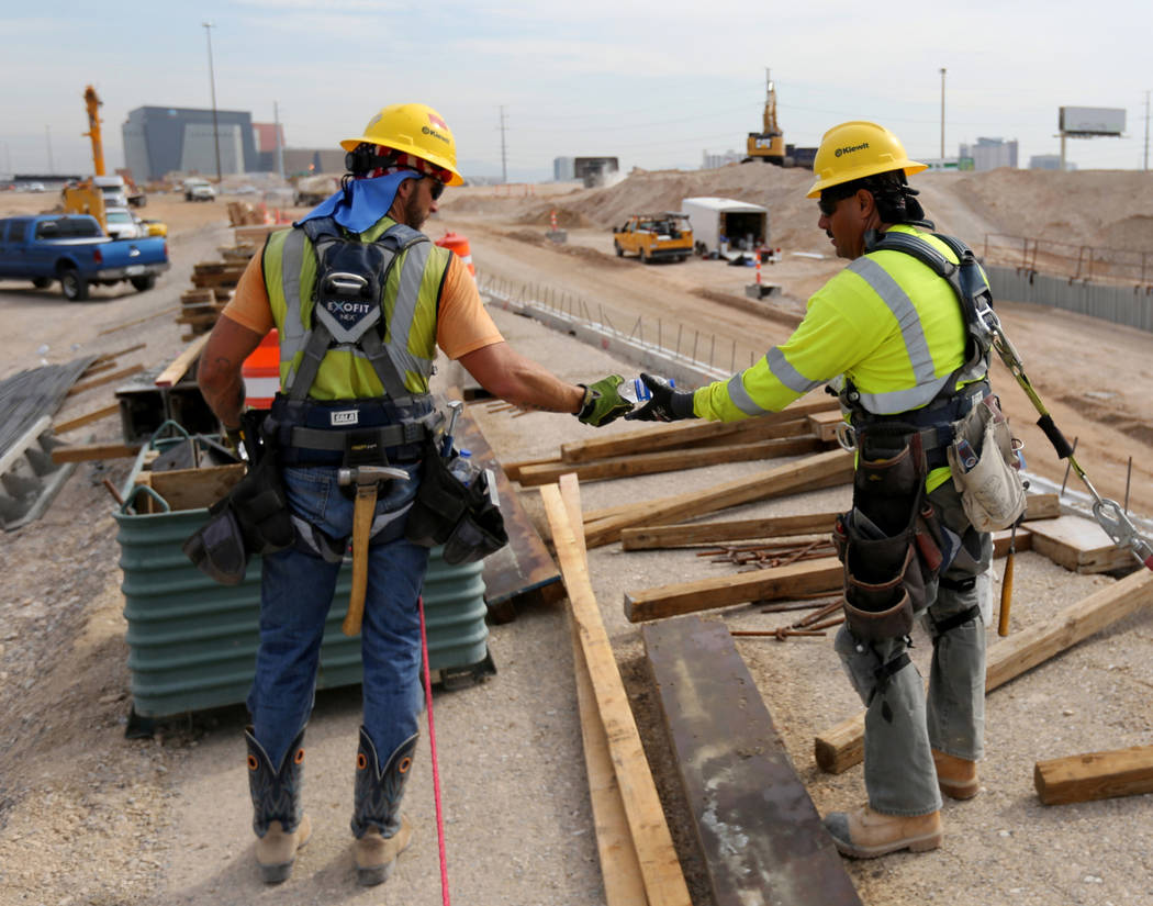 Workers share water while working Nevada Department of Transportation Project Neon on Interstate 15 between the Spaghetti Bowl and Sahara Avenue Thursday, Aug. 2, 2018. K.M. Cannon Las Vegas Revie ...