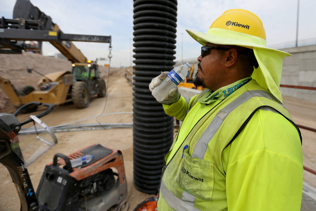 """Jaime Martinez drinks water while working on a retaining wall for the """"Neon Gateway"""" high-occupancy vehicle exit ramps as part of Nevada Department of Transportation Project Neon on Inte ..."""