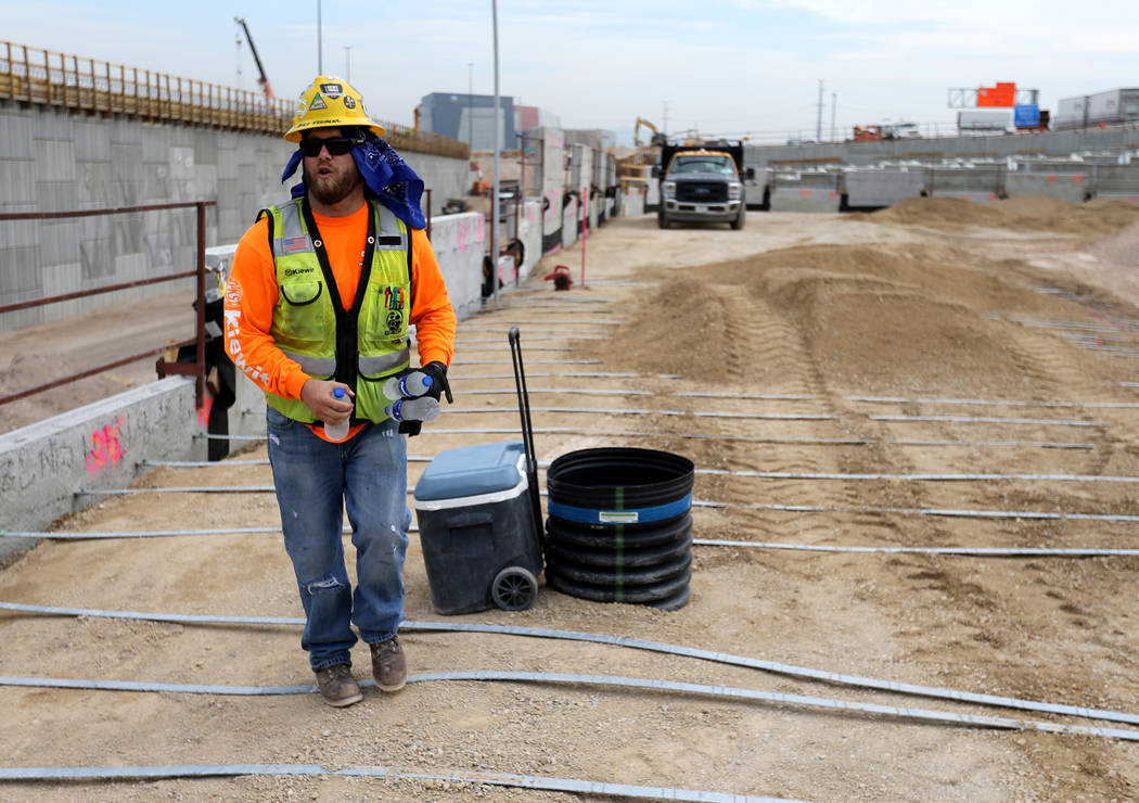 """Mike Yedinak grabs bottles of water for his crew working on a retaining wall for the """"Neon Gateway"""" high-occupancy vehicle exit ramps as part of Nevada Department of Transportation Proje ..."""