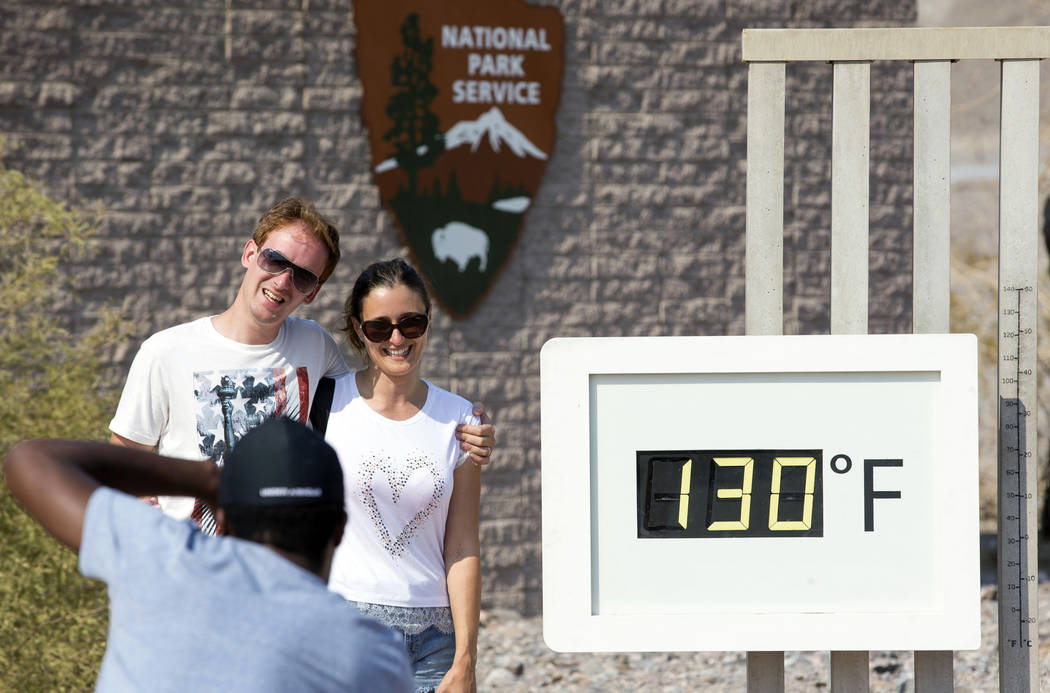 A couple poses at the Furnace Creek Visitor Center thermometer in Death Valley National Park, Calif., Thursday, July 26, 2018. (Richard Brian/Las Vegas Review-Journal)