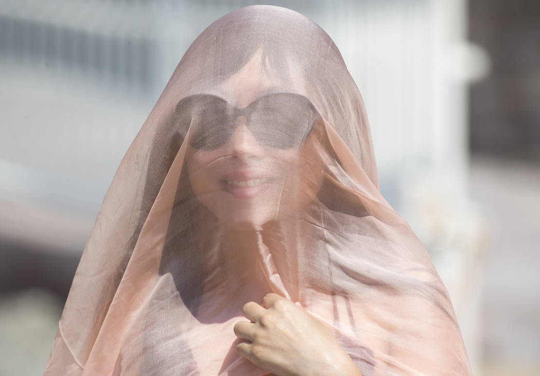 Sherry Chen of China shades herself from the sun with a thin pink veil while visiting Badwater Basin, 282 feet below sea level, in Death Valley National Park, Calif., Thursday, July 26, 2018. Rich ...