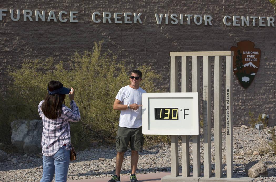 Los residentes de Las Vegas Cory Pérez, izquierda, y Jon Bach se toman fotos en el termómetro del Furnace Creek Visitor Center en el Parque Nacional Death Valley, California, el jueves 26 de jul ...