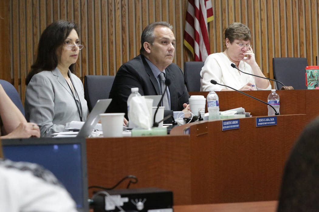 Clark County School District Superintendent, Jesus Jara, center, listens to a presentation to the board with Elizabeth Carrero, secretary to the superintendent, left, and Deanna L. Wright, truste ...
