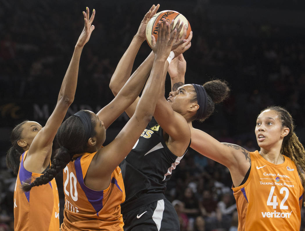Aces forward Nia Coffey (12) shoots over Phoenix Mercury defenders Camille Little (20), Brittney Griner (42) and DeWanna Bonner (24) in the first quarter on Wednesday, August, 1, 2018, at the Mand ...