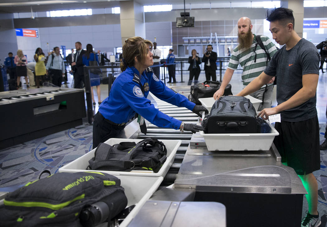 Transportation Security Administration agent Donna Franco, left, assists a passenger in one of the new automated screening lanes at McCarran International Airport Terminal 3 in Las Vegas, on Thurs ...
