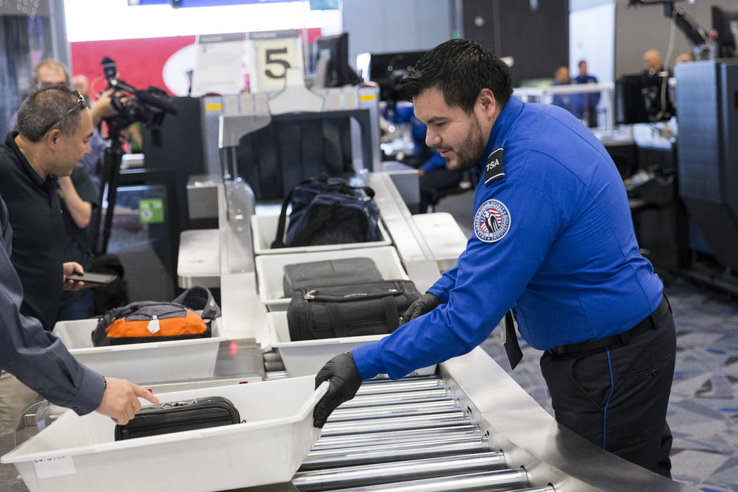 Transportation Security Administration agent Eduardo Puga, right, assists a passenger in one of the new automated screening lanes at McCarran International Airport Terminal 3 in Las Vegas, on Thur ...