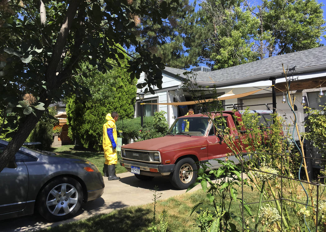 In this Tuesday, July 31, 2018 photo workers clean up a home where a homeowner shot and killed an intruder and was then killed by police responding to calls of a disturbance in Aurora, Colo. just ...