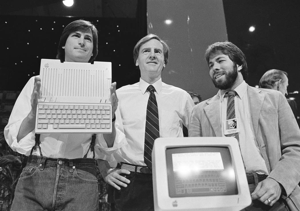Steve Jobs, left, chairman of Apple Computers, John Sculley, president and CEO, and Steve Wozniak, co-founder of Apple, unveil the new Apple IIc computer in San Francisco, California, April 24, 19 ...