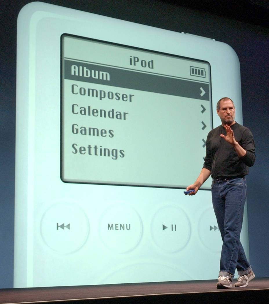"Apple Computer Inc. chief executive Steve Jobs gestures as he introduces the new iPod during Apple's launch of their new online ""Music Store"" in San Francisco, April 28, 2003. (AP, File)"