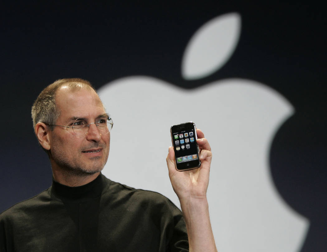 Apple CEO Steve Jobs holds up the new iPhone during his keynote address at MacWorld Conference & Expo in San Francisco. (Paul Sakuma/AP, File)
