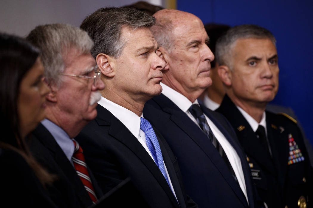 FBI Director Christopher Wray listens during the daily press briefing at the White House, Thursday, Aug. 2, 2018, in Washington. From left also listening are White House press secretary Sarah Huck ...