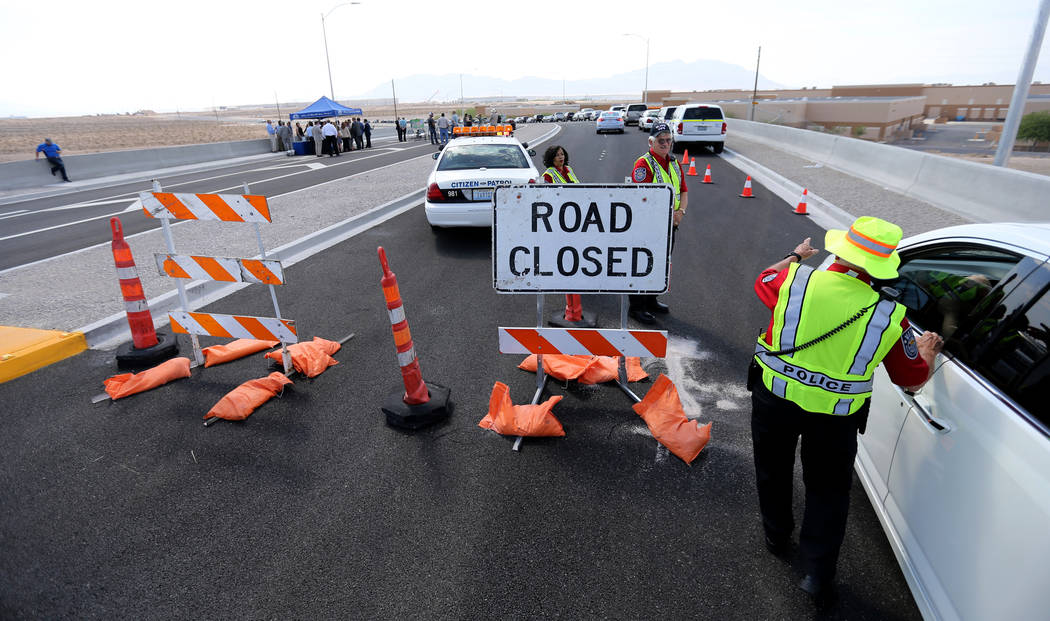 Bill Foster, of North Las VegasVolunteers in Police Services, directs guests to a ceremony marking the opening of Tropical Parkway connector to the Interstate 15 and the Las Vegas Beltway in ...