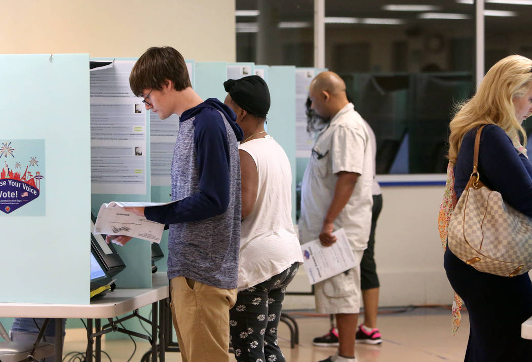 Voters, including Steven Roman, 18, of Las Vegas, cast their vote during Tuesday's primary election at a polling station at Kenny G. Guinn Middle School on June 12, 2018, in Las Vegas. Bizuayehu T ...