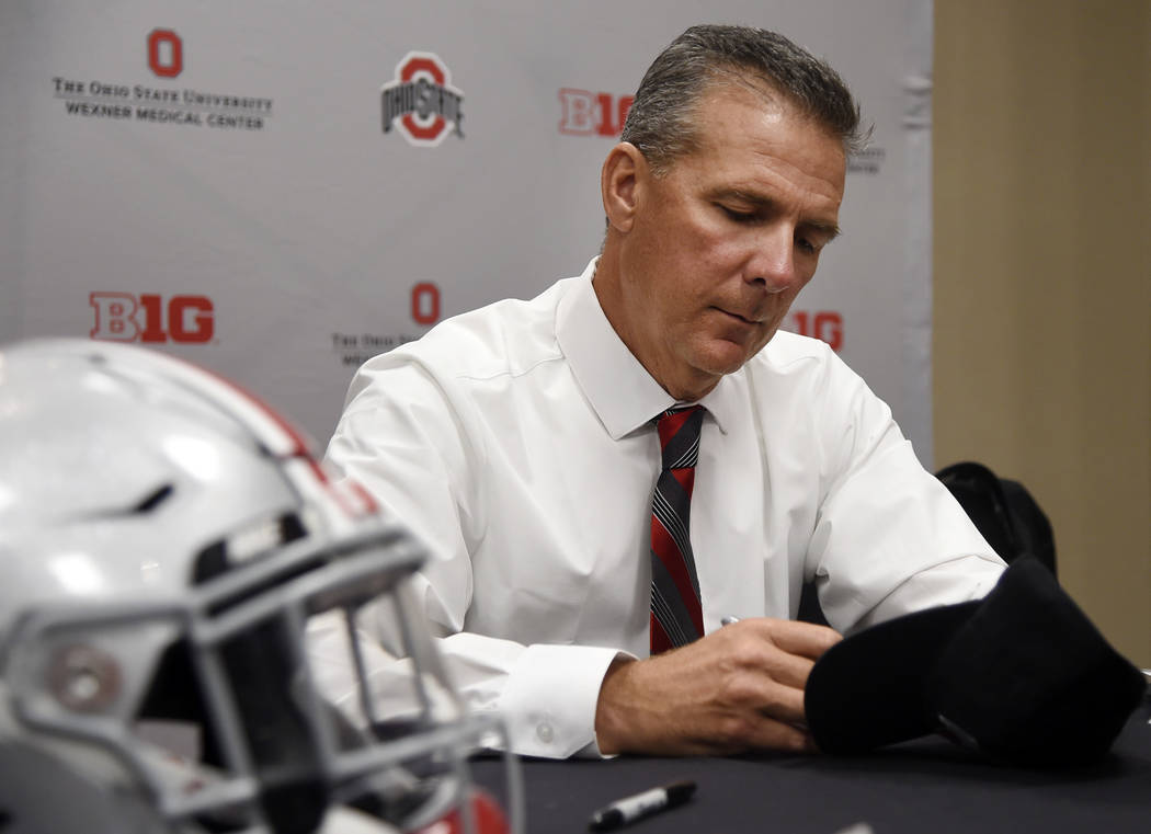 Ohio State head coach Urban Meyer autographs a hat at the Big Ten Conference NCAA college football media days in Chicago, Tuesday, July 24, 2018. (AP Photo/Annie Rice)