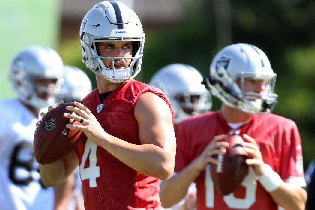 Quarterback Derek Carr (4) prepares to throw the football alongside quarterback Connor Cook (18) at the Oakland Raiders training camp in Napa, Calif., Friday, July 27, 2018. Heidi Fang Las Vegas R ...