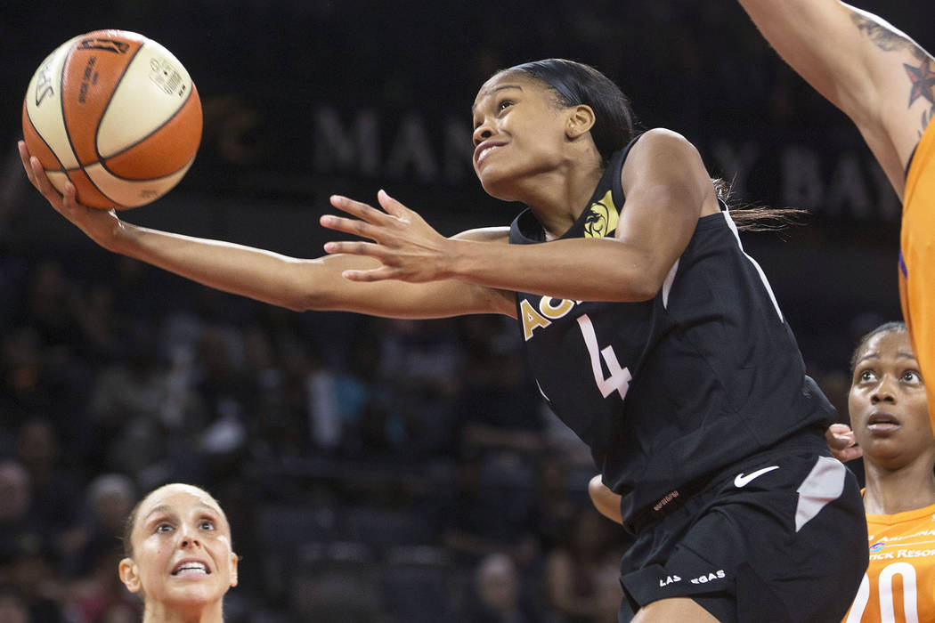 Aces guard Moriah Jefferson (4) drives past Phoenix Mercury defenders Brittney Griner (42) and Diana Taurasi (3) in the second quarter on Wednesday, August, 1, 2018, at the Mandalay Bay Events Cen ...