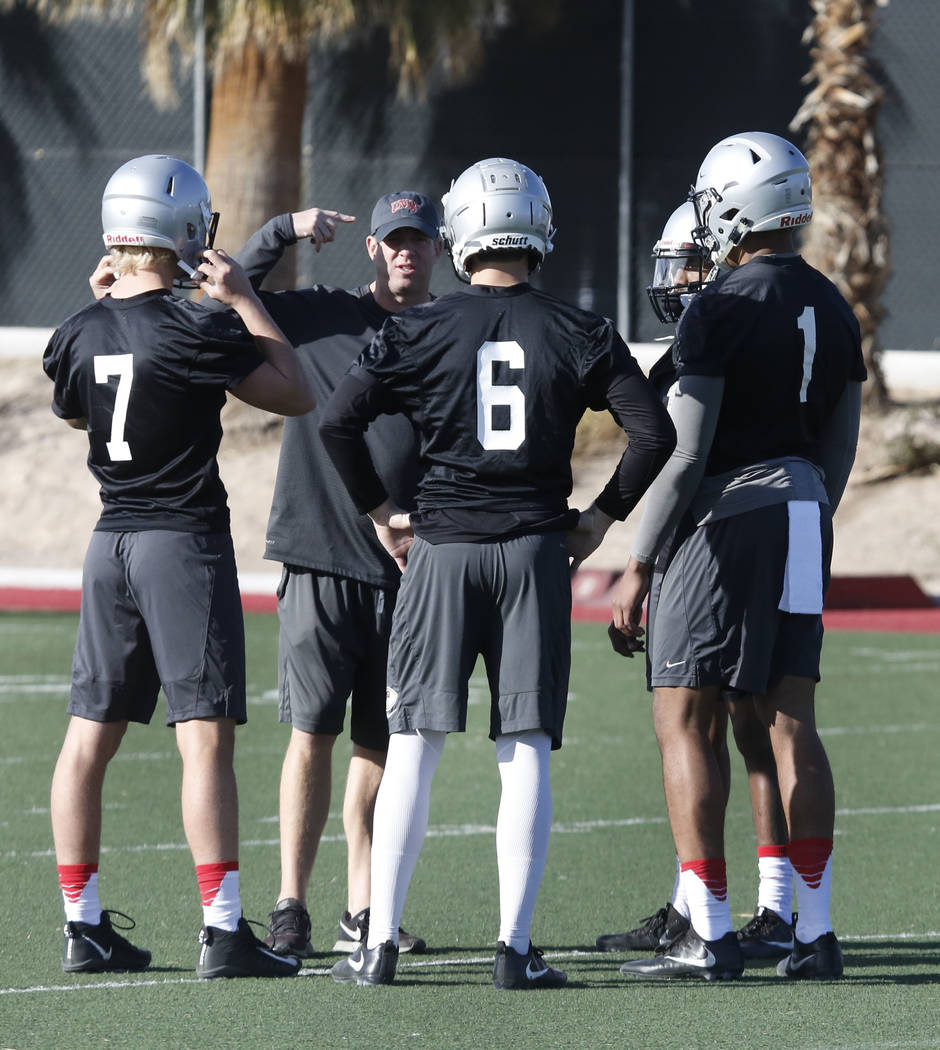 Ron O'Dell, UNLV quarterback coach, second left, chats with quarterbacks Kenyon Oblad (7) Armani Rogers (1) Max Gilliam (6) and Marckell Grayson (15) during the first day of spring practice ...