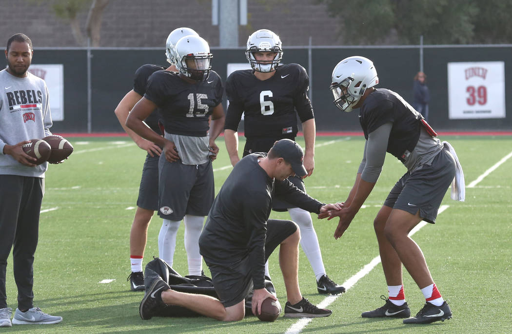 Ron O'Dell, UNLV quarterback coach, center, works with quarterbacks Armani Rogers, right, Max Gilliam (6) and Marckell Grayson (15) during team practice on Tuesday, March 13, 2018, in Las V ...