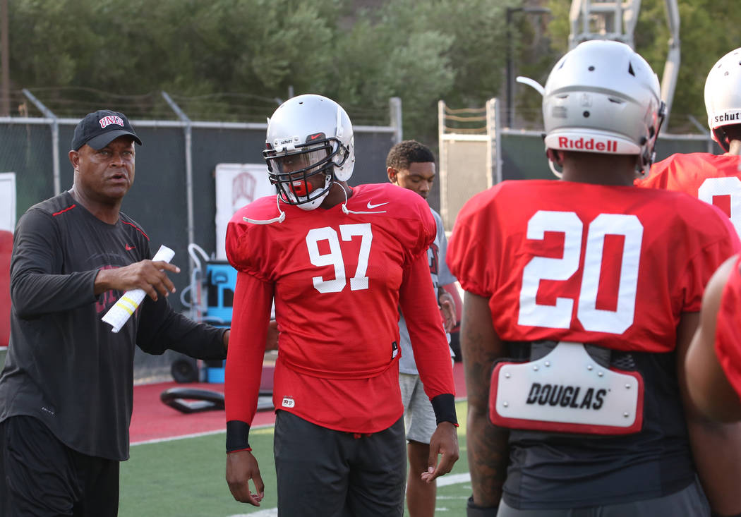 UNLV's defensive line coach Tony Samuel gives instruction to defensive lineman Jamal Holloway (97) and defensive end Jameer Outsey (20) during team practice on Thursday, Aug. 9, 2018, in Las Vegas ...