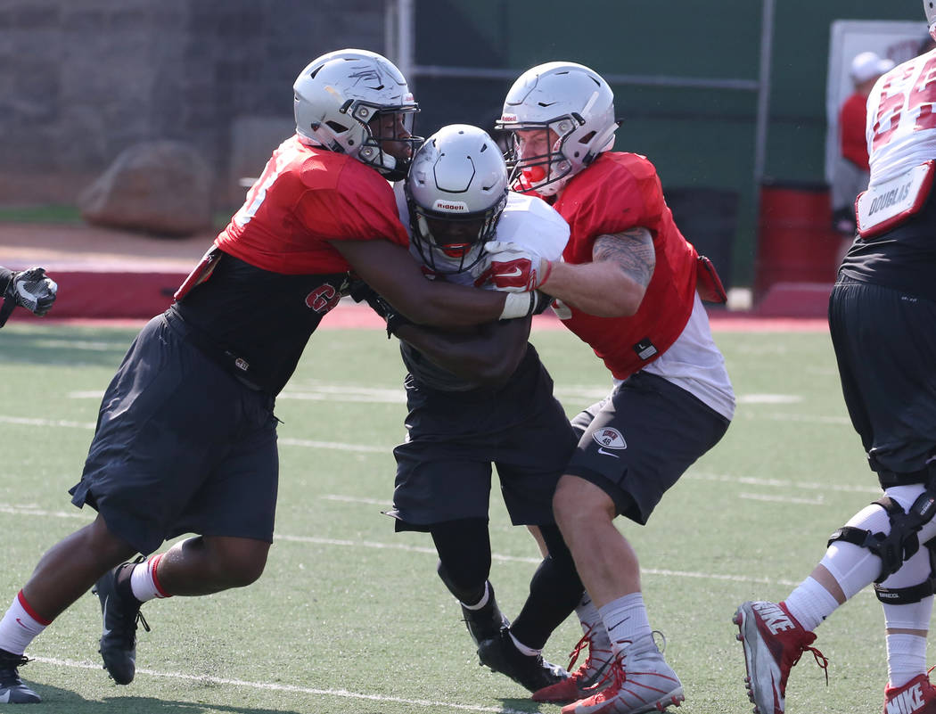 UNLV running back Charles Williams, center, tackled by linebackers Farrell Hester II, left, and Bailey Laolagi during team practice on Thursday, Aug. 9, 2018, in Las Vegas. Bizuayehu Tesfaye/L ...