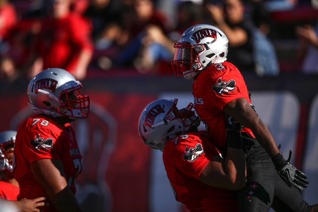 UNLV Rebels offensive lineman Jaron Caldwell (75), center, lifts running back Lexington Thomas (3), right, after he scored a touchdown against the Utah State Aggies during the second quarter of a ...