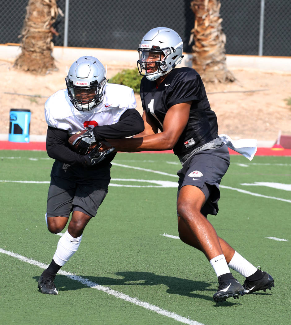 UNLV running back Lexington Thomas (3) takes the handoff from quarterback Armani Rogers (1) during team practice on Thursday, Aug. 9, 2018, in Las Vegas. Bizuayehu Tesfaye/Las Vegas Review-Journal ...