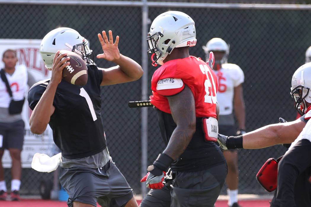 UNLV's defensive end Jameer Outsey (20) tries to block quarterback Armani Rogers' (1) throw during team practice on Thursday, Aug. 9, 2018, in Las Vegas. Bizuayehu Tesfaye/Las Vegas Review-Journal ...