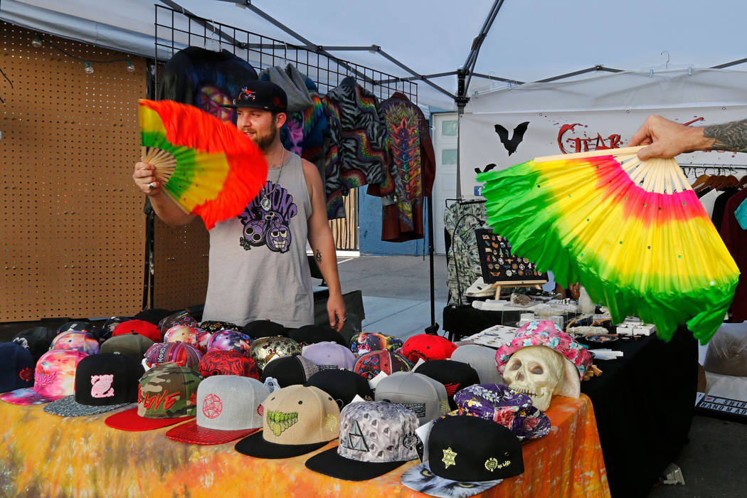 Gear and Clothing In Las Vegas co-owner Cal McAlvain uses a fan to cool off while selling the items during First Friday Las Vegas, a monthly art festival, located in downtown Las Vegas Arts Distri ...