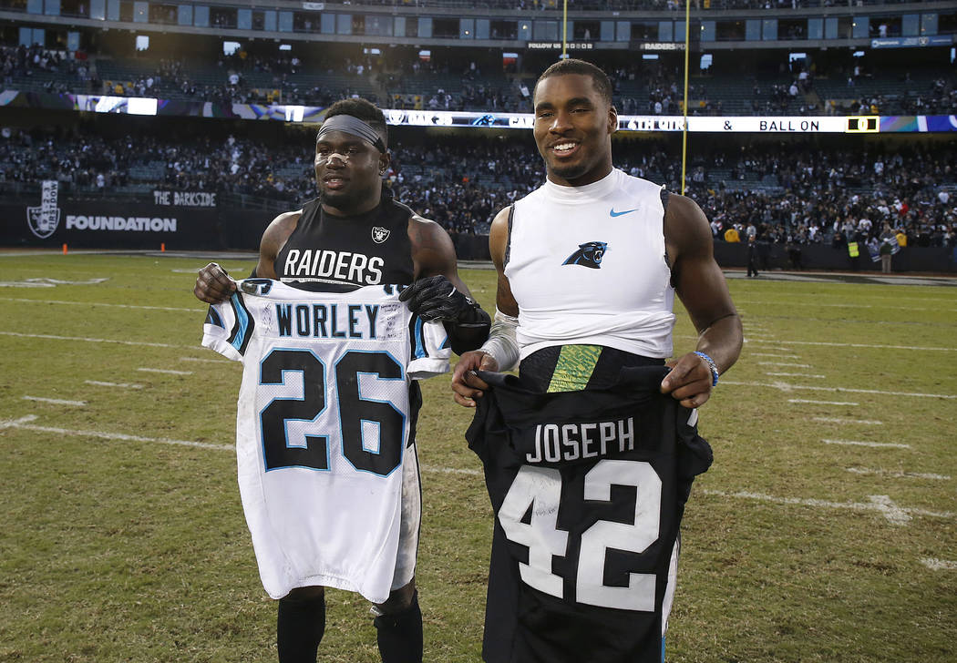 Oakland Raiders safety Karl Joseph, left, and Carolina Panthers cornerback Daryl Worley pose for photos after swapping jerseys after an NFL football game in Oakland, Calif., Sunday, Nov. 27, 2016. ...