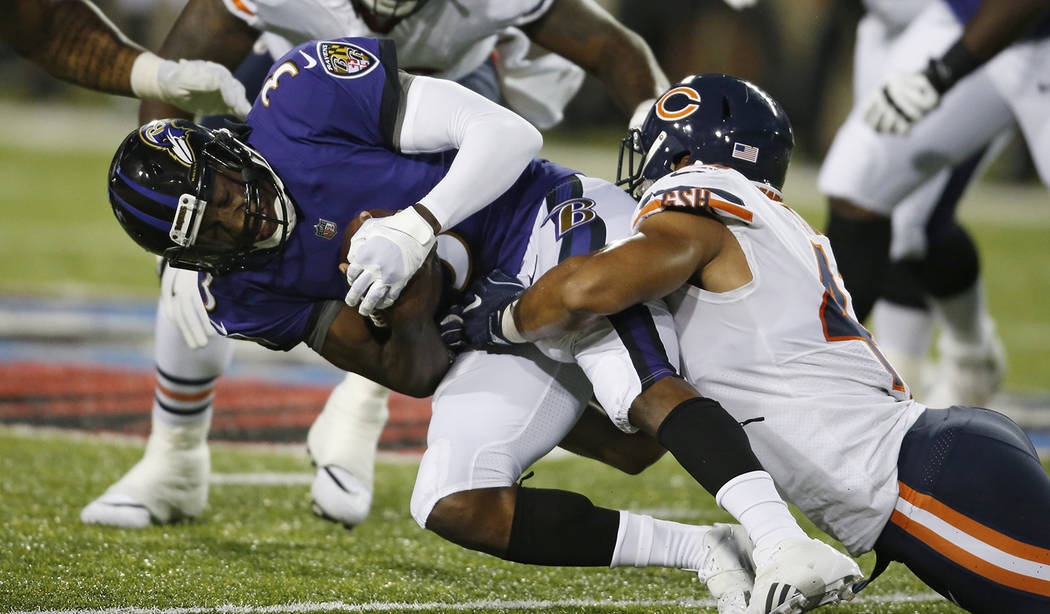 Chicago Bears linebacker Isaiah Irving, right, tackles Baltimore Ravens quarterback Robert Griffin III (3) during the first half of the Pro Football Hall of Fame NFL preseason game Thursday, Aug. ...