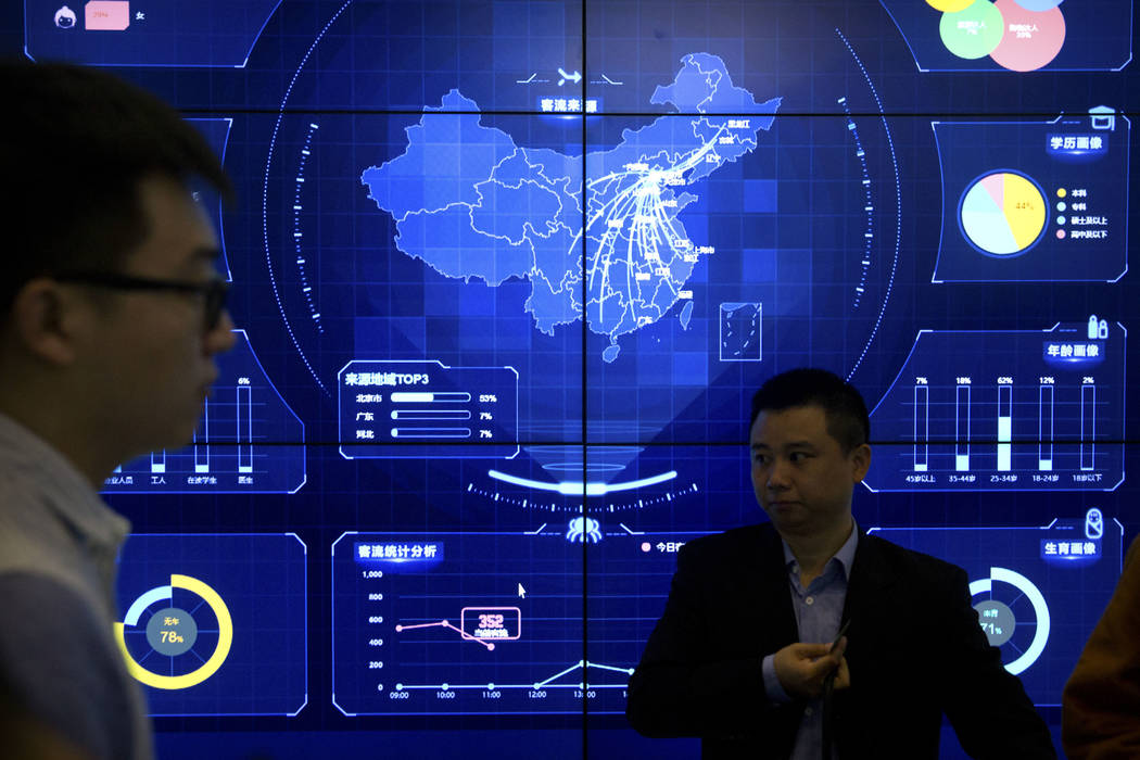 In this April 26, 2018, photo, visitors stand in front of an electronic data display showing a map of China at the Global Mobile Internet conference in Beijing. A California-based security-researc ...