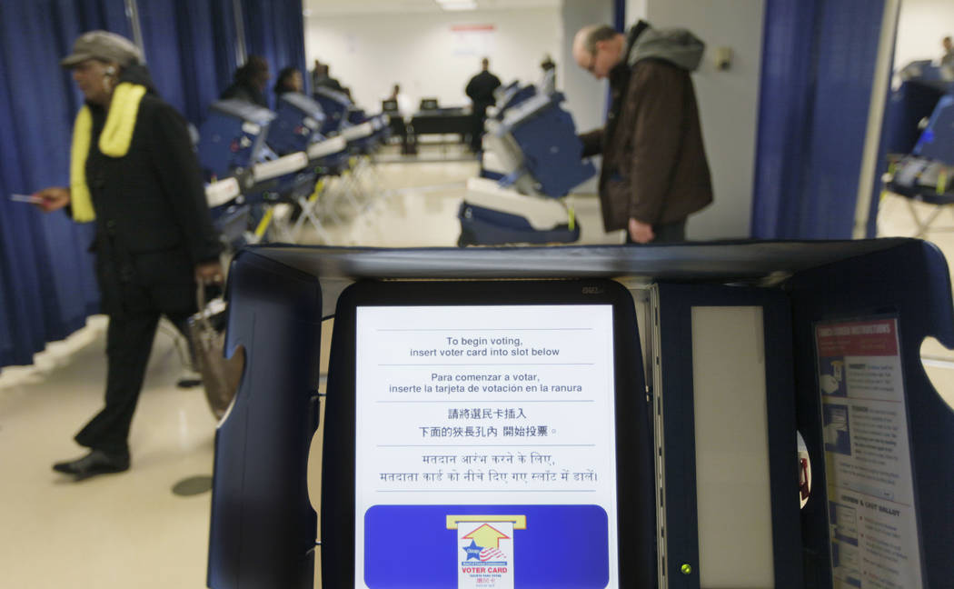 In this Feb. 27, 2012 file photo, voters cast their ballots during early voting at the Board of Elections building, in downtown Chicago. Illinois is set to receive $13.9 million in federal funds a ...