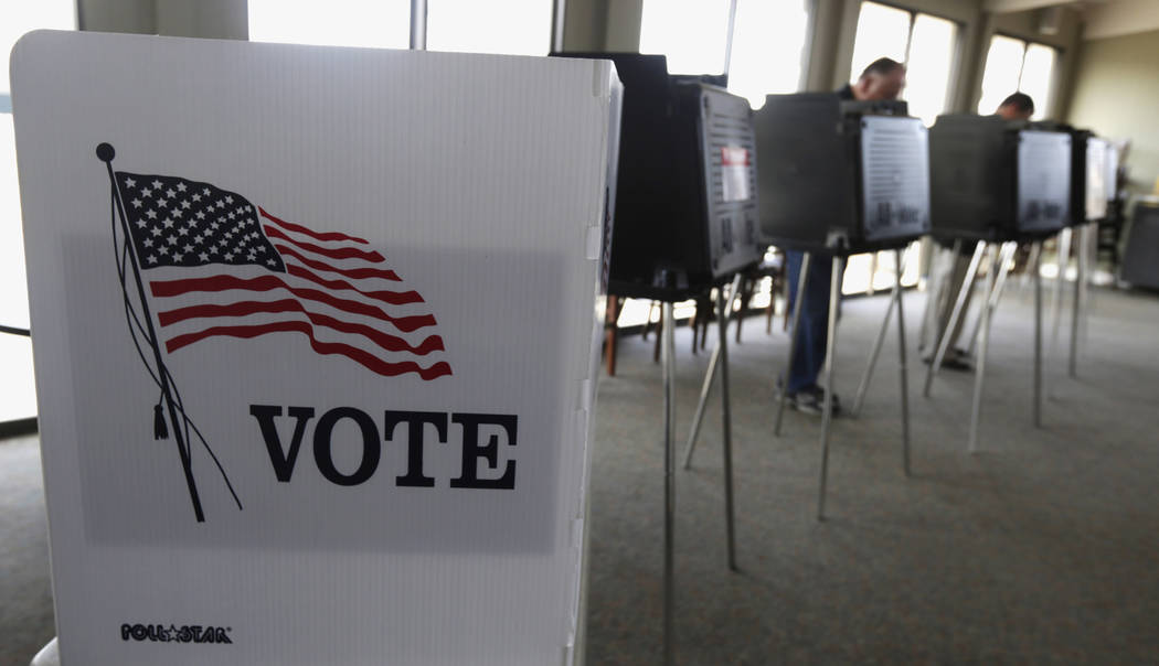 In this March 18, 2014 file photo, voters cast their ballots in Hinsdale, Ill. Illinois is set to receive $13.9 million in federal funds after Russian hackers breached the state's voter registrati ...