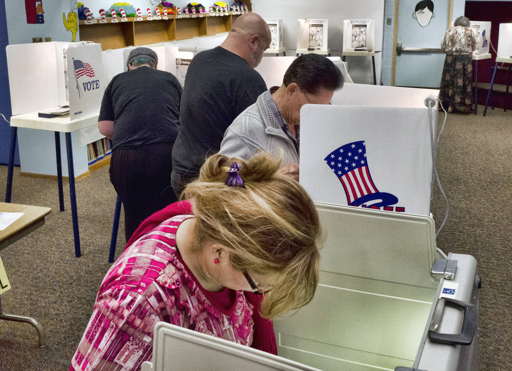 This June 5, 2018 file photo shows people marking their ballots at a polling station at Robert F. Kennedy Elementary School in Los Angeles. A security review found a software error caused a proble ...