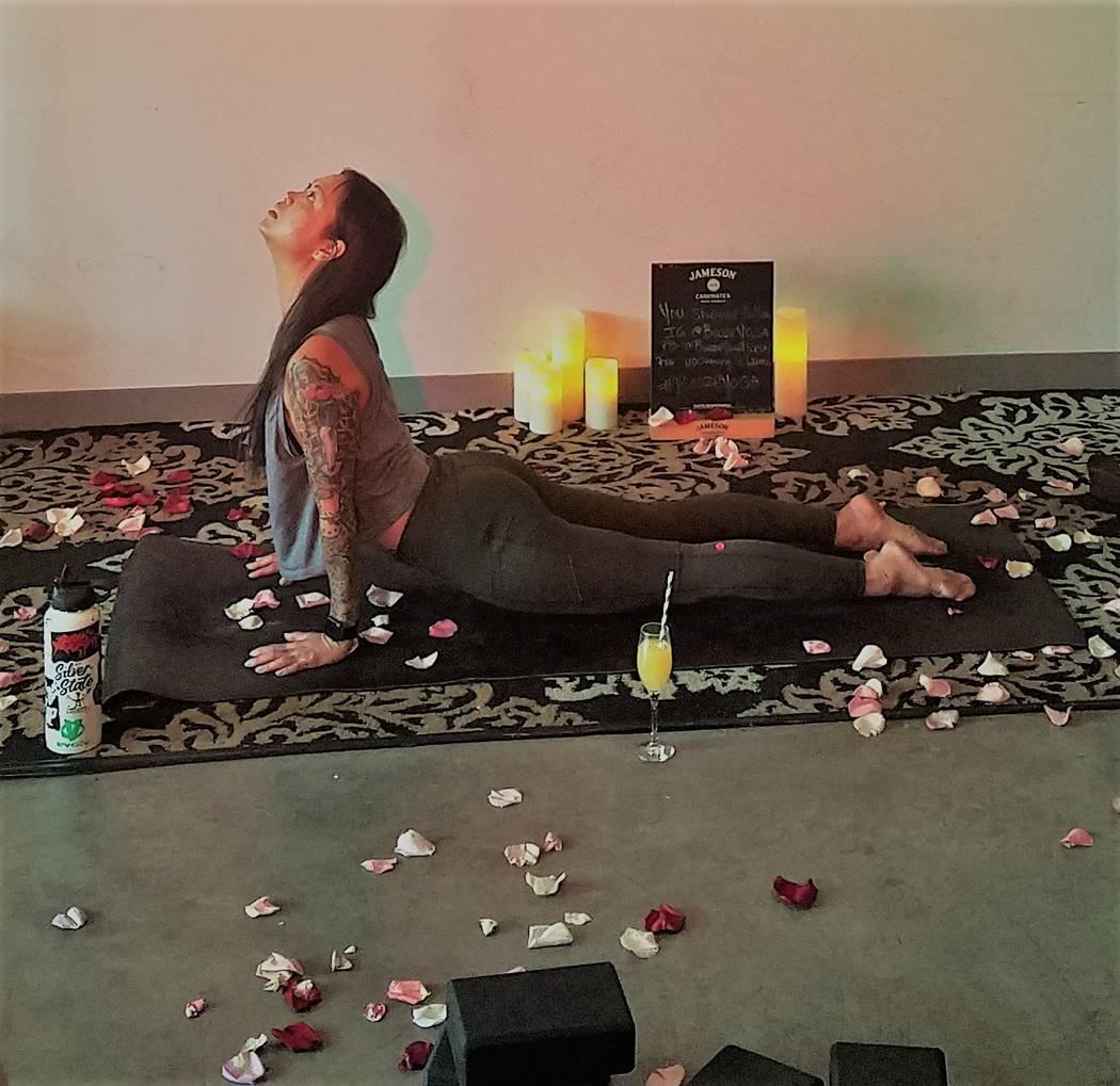 Tas Upright leads a Booze Yoga class at Cork & Thorn in Tivoli Village. (Tony Alexander)