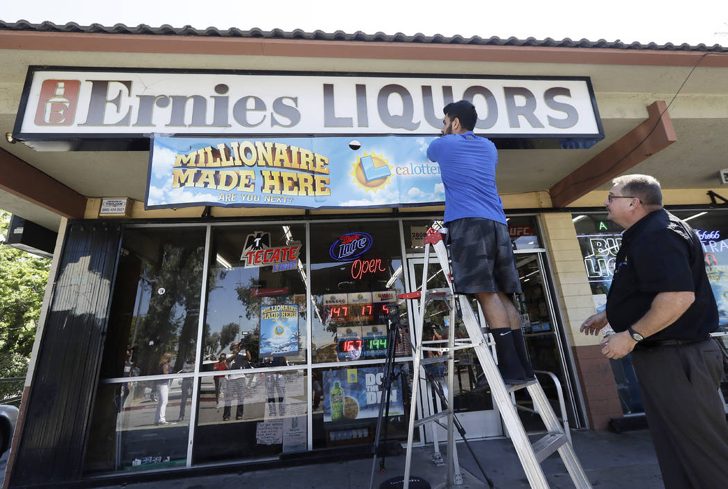 In this July 25, 2018 file photo, California Lotteryofficial Mike Neis, right, watches as Amol Sachdev hangs a sign over his family's store Ernie's Liquors where a Mega Millions lottery ticket w ...