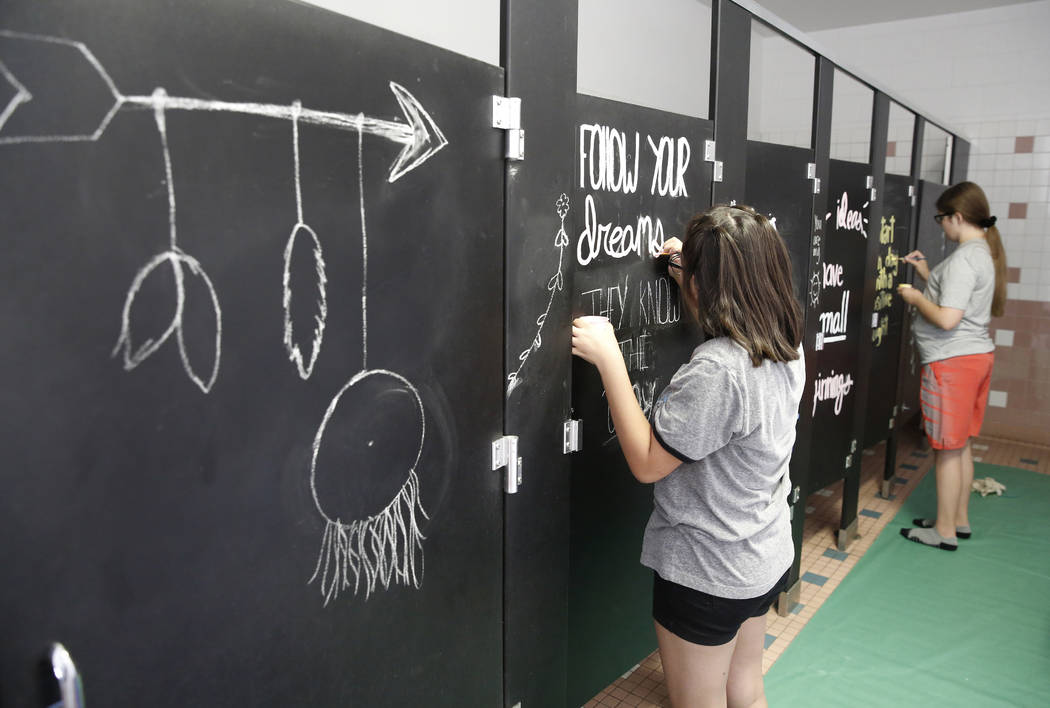 Mojave High School students Leslie Garcia, 16, left, and Lindsay Hurst, 15, paint inspirational messages on their school bathroom doors on Friday, Aug. 3, 2018, in Las Vegas. Bizuayehu Tesfaye/Las ...