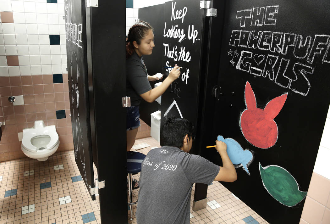 Mojave High School students Ashley Macias, 16, left, and Daniel Carbajal, 16, paint inspirational messages on their school bathroom doors on Friday, Aug. 3, 2018, in Las Vegas. Bizuayehu Tesfaye/L ...