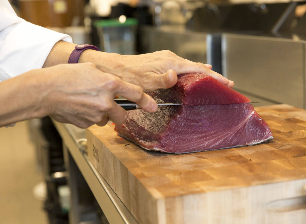 Japanese sushi chef Miho Akasaka prepares ahi tuna for sashimi and nigiri in the kitchen at the new Boathouse restaurant at Palace Station in Las Vegas on Friday, Aug. 3, 2018. Richard Brian Las V ...
