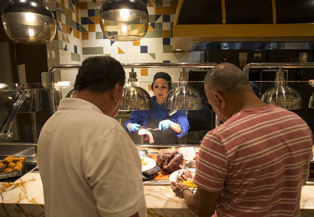 Cook Stephanie Cisneros serves prime rib to customers at the Blazing Grill station at the new Feast Buffett at the newly renovated Palace Station hotel-casino in Las Vegas on Friday, Aug. 3, 2018. ...